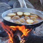 Bratkartoffeln in einer Pfanne über offenem Lagerfeuer.