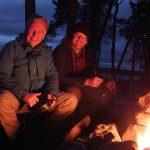 Zwei Männer sitzen nachts am Lagerfeuer